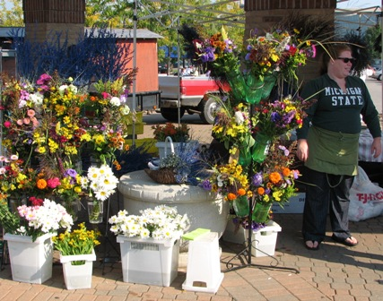 A vendor sells flowers at the Holland Farmers' Market.